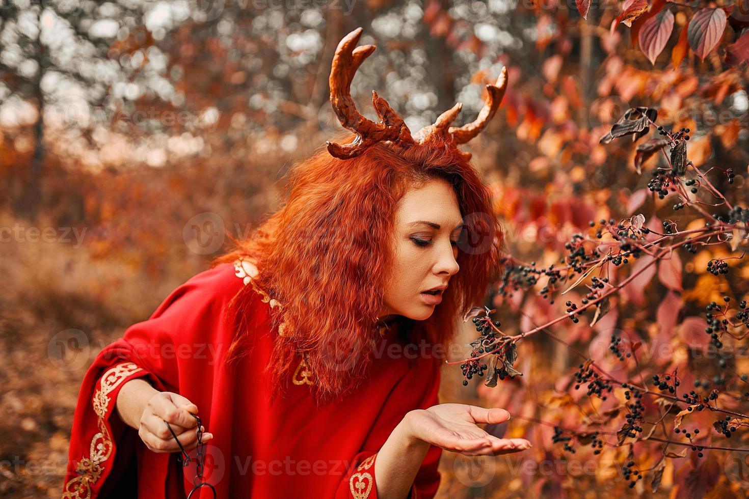 mujer en vestido rojo largo con cuernos de venado en el bosque de otoño. foto