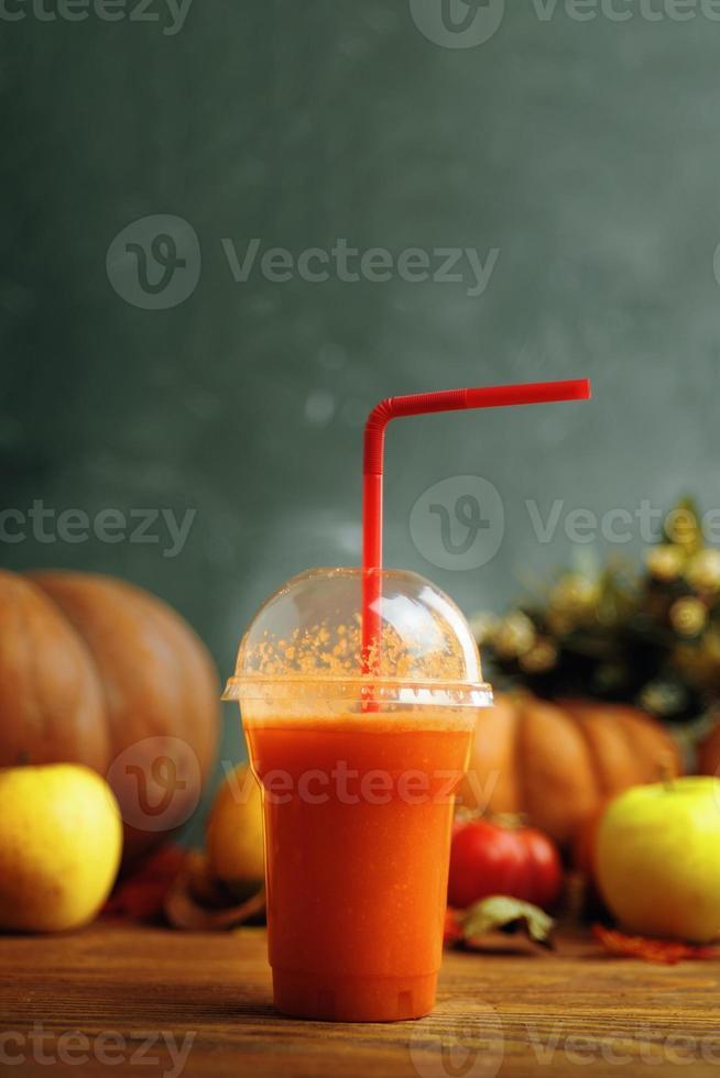 Pumpkins juice in bottles with pumpkins. photo