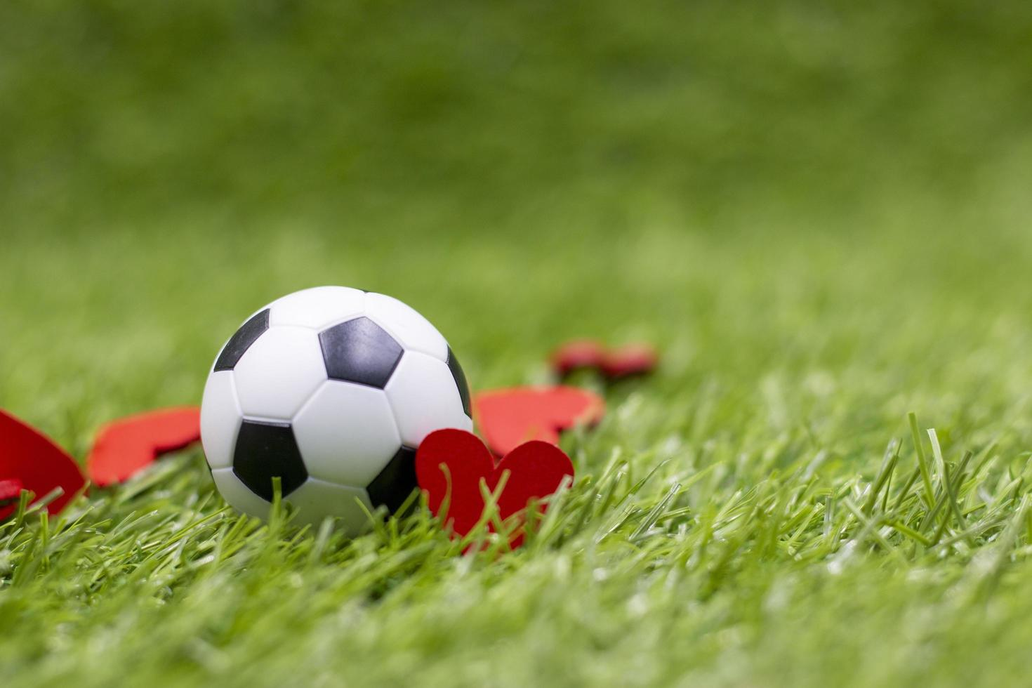 Soccer ball is on green grass with love red heart photo