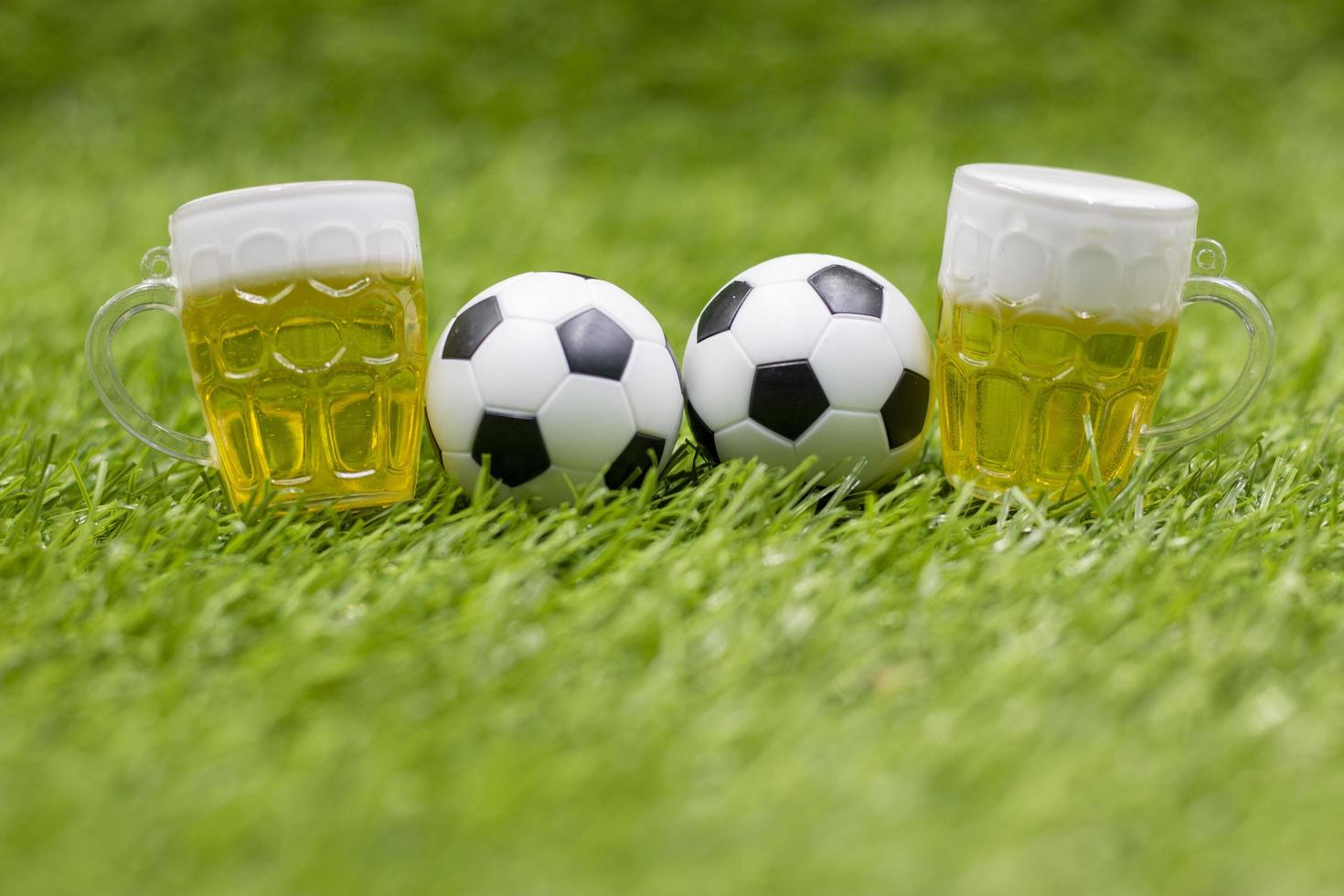 Soccer ball and glass of beer are on green grass photo