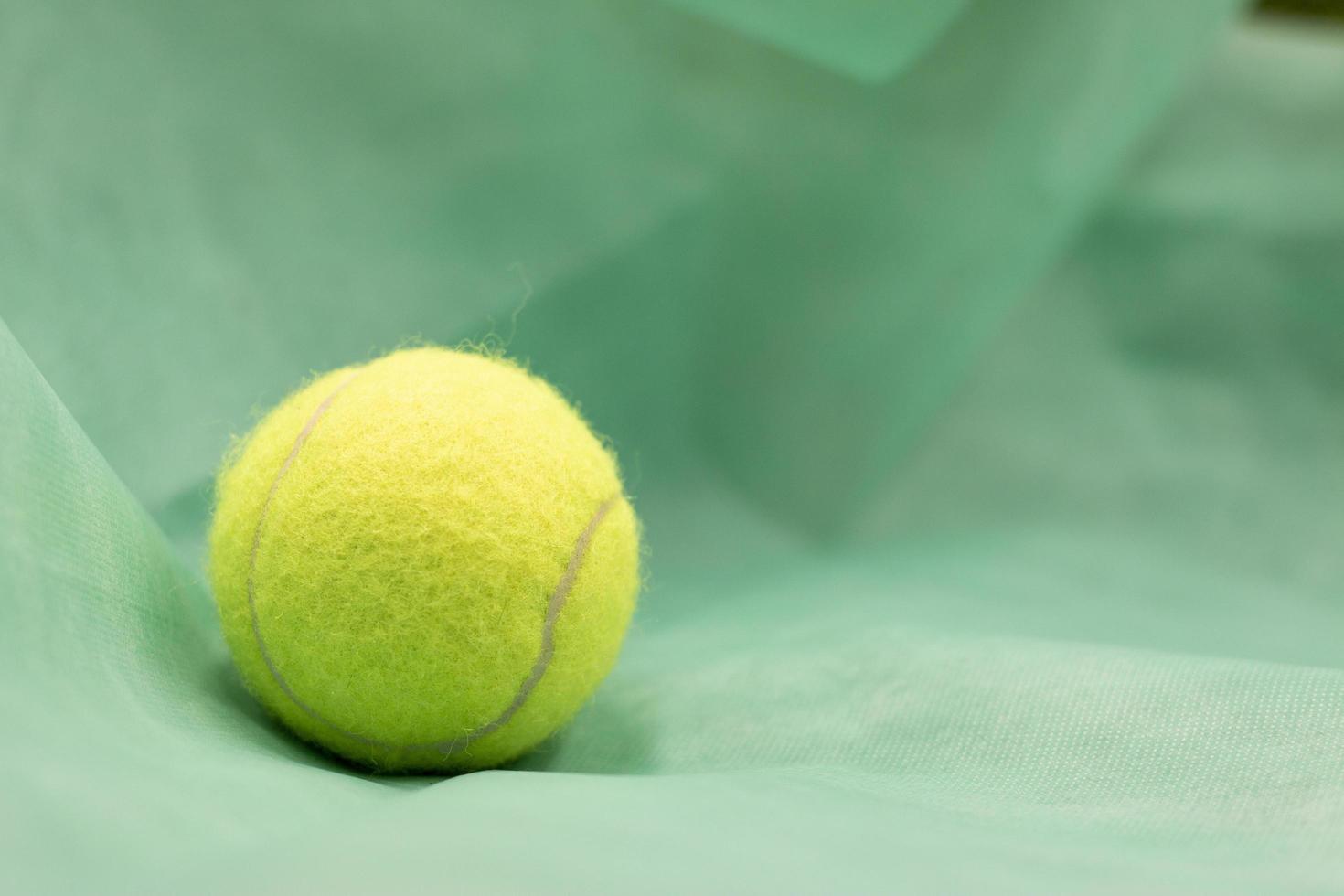 pelota de tenis está sobre fondo verde foto