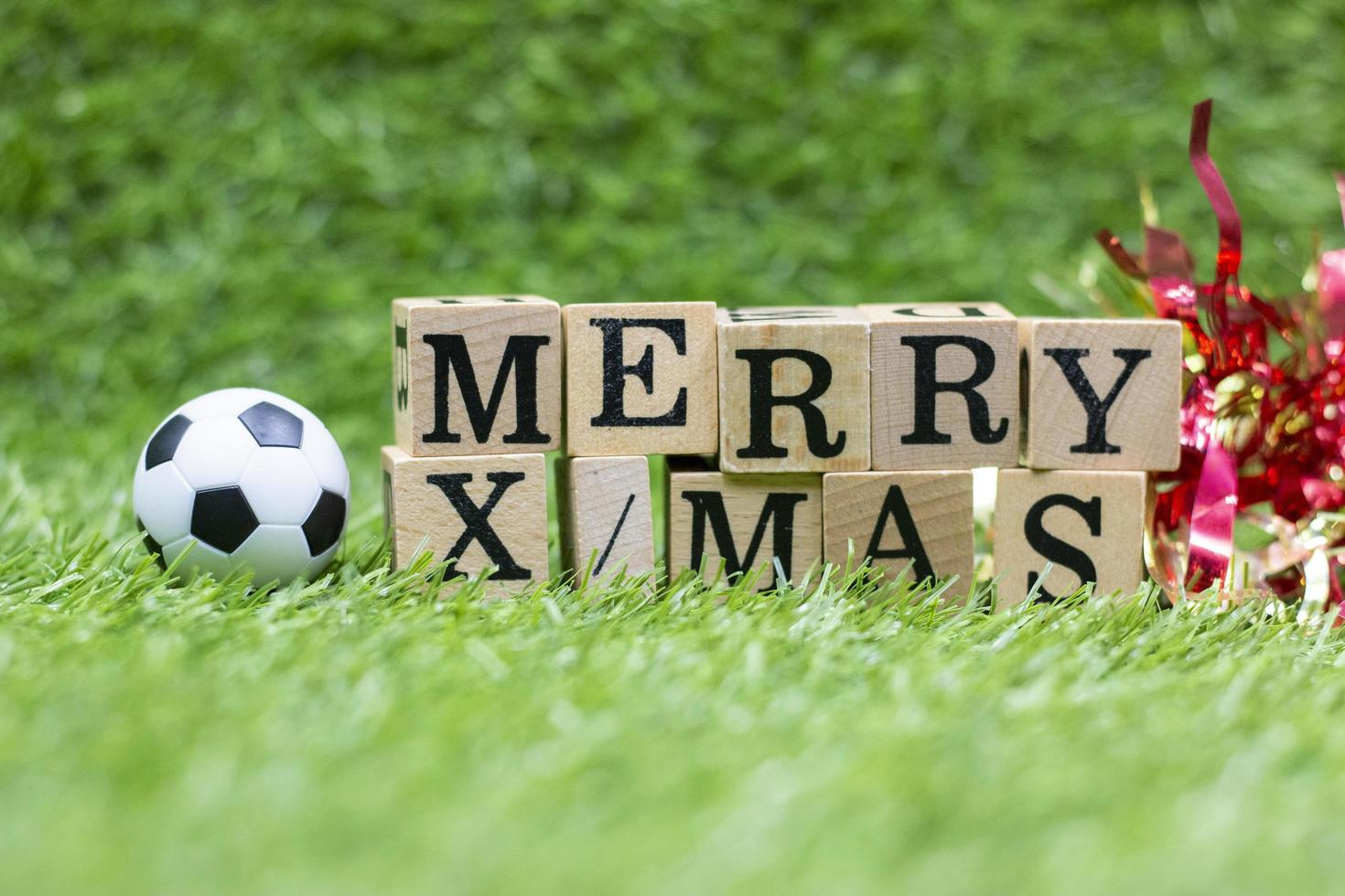 Soccer ball with Merry Xmas text on green grass photo