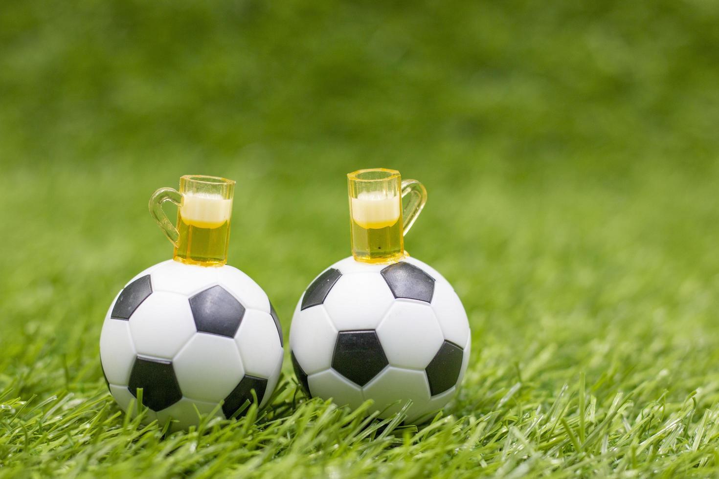 Balón de fútbol con vasos de cerveza sobre la hierba verde foto