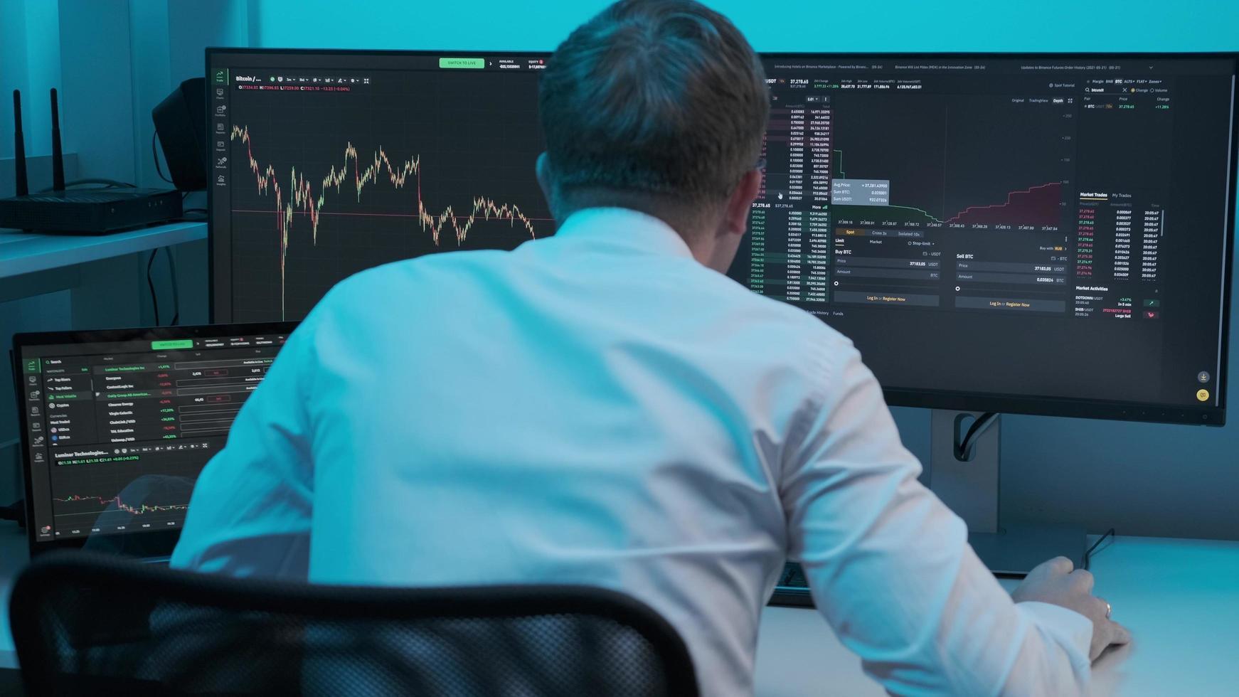 Cerca del joven comerciante caucásico que trabaja en la computadora del monitor y navega en línea en la oficina comercial. corredor masculino siguiendo tasas y apuestas. foto