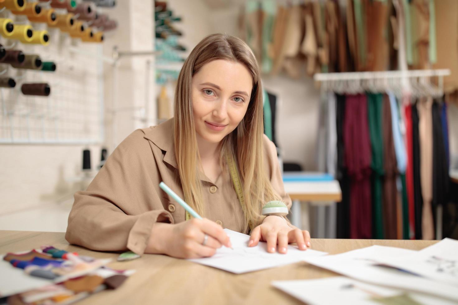 Mujer joven diseñando vestidos de moda y dibujando con lápices de colores varios dibujos de moda coloridos foto