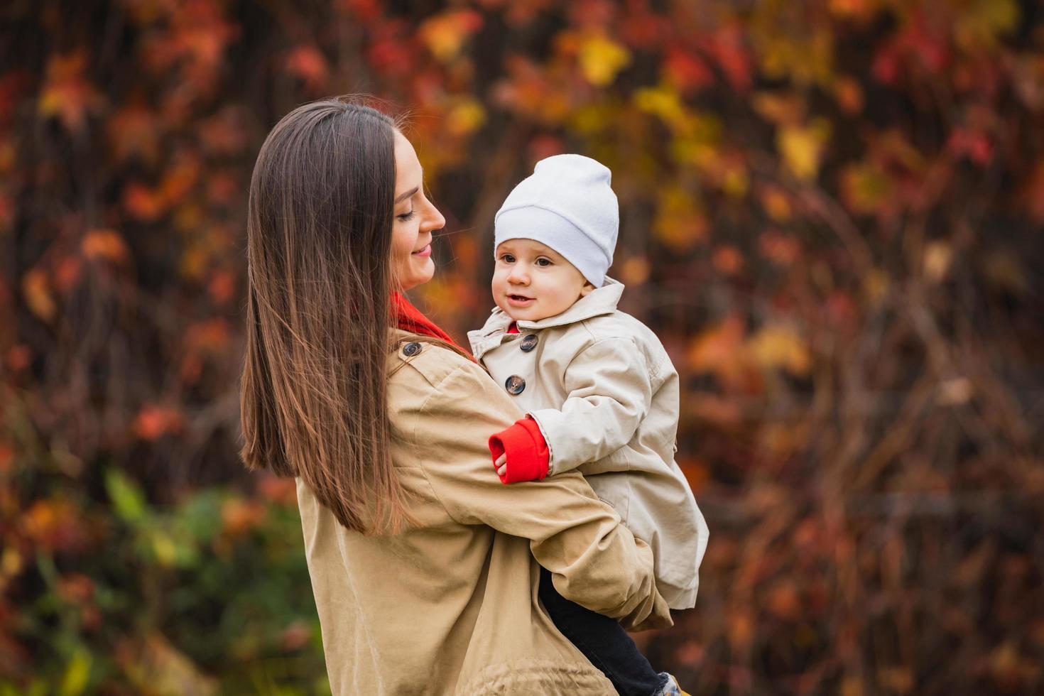 bahía con mamá en el parque de otoño. mamá e hija en el otoño. mamá sostiene al bebé en sus brazos. madre con su pequeña hija en el parque de otoño en un paseo. foto