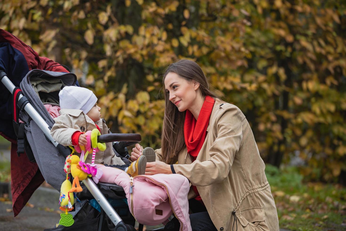 la madre está poniendo zapatos pequeños a su bebé en el parque de otoño foto