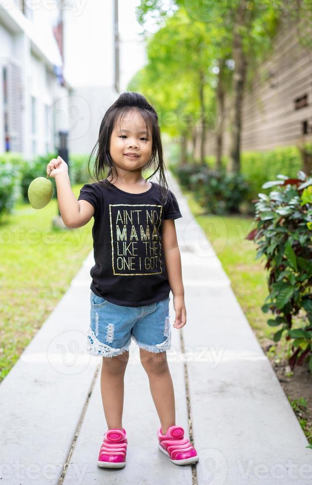 niña con un mango en la mano foto