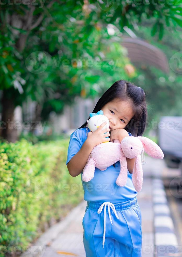 Cute little asian girl with a doll in the park photo