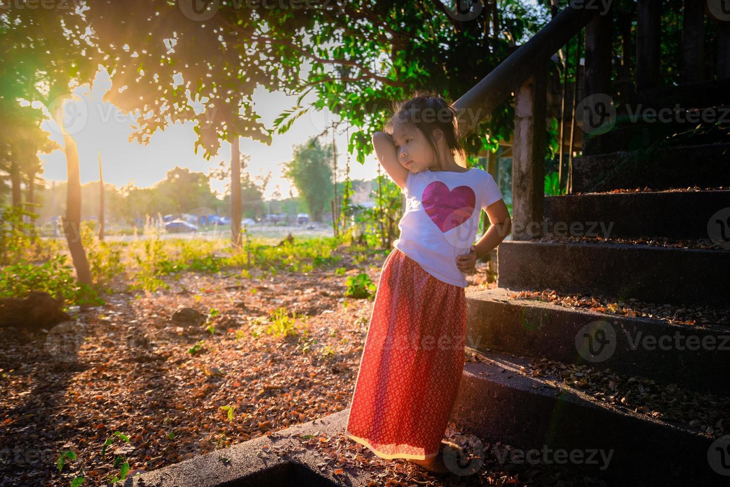 Retrato de feliz niña asiática de pie en el parque con la luz del sol foto
