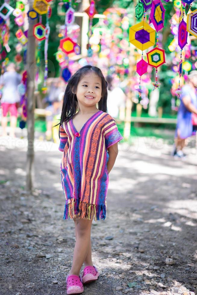 retrato, de, feliz, niña asiática, en, vestido, con, tung, banderas, posición, en, el, parque foto