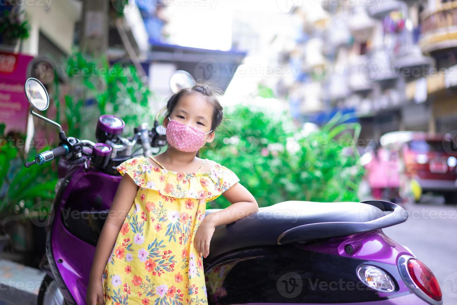 Niña asiática con una máscara contra el anochecer y covid-19 al aire libre foto