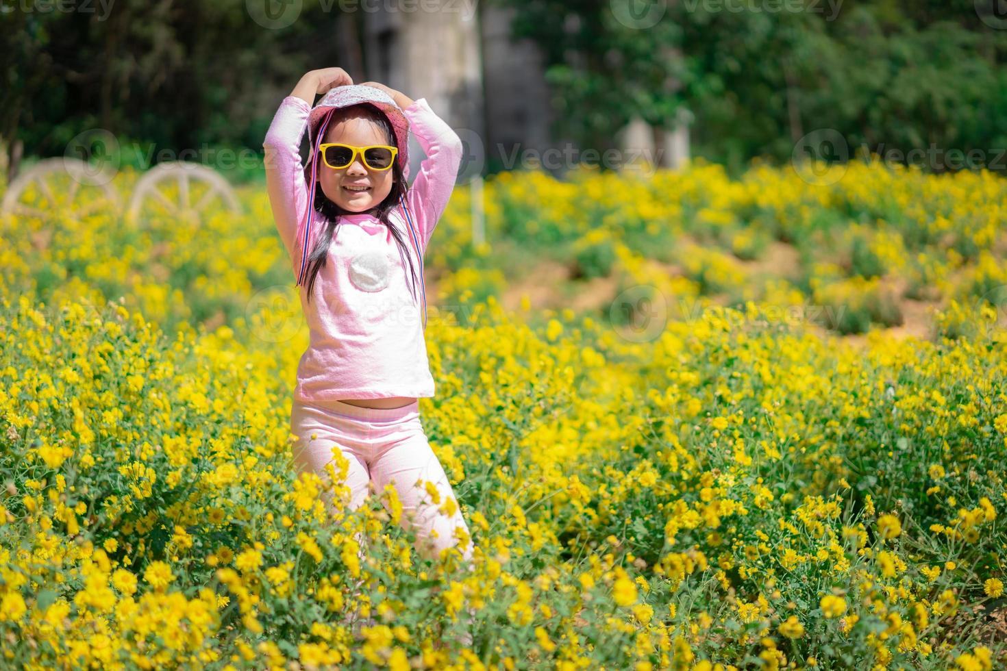 Niña asiática en vestido rosa usar sombrero y gafas de sol de pie en el jardín de flores amarillas foto