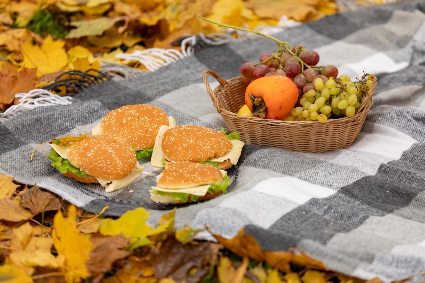 picnic de otoño en el bosque, la manta se encuentra sobre hojas amarillas caídas. fruta en una canasta y hamburguesas foto