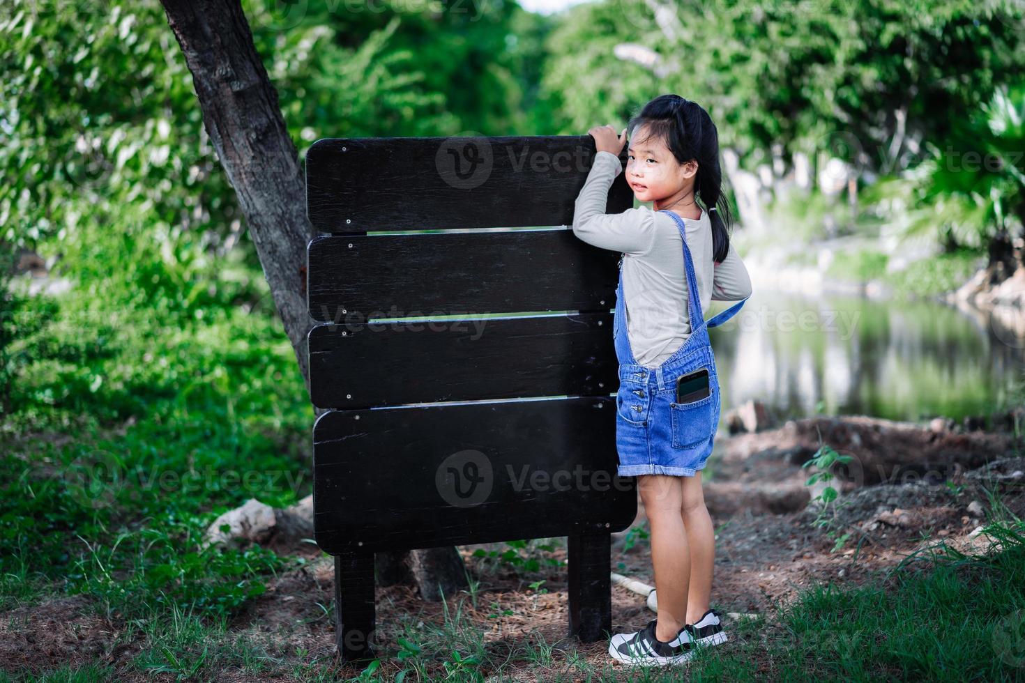 niña asiática pone el teléfono móvil en el bolsillo con etiqueta de madera foto