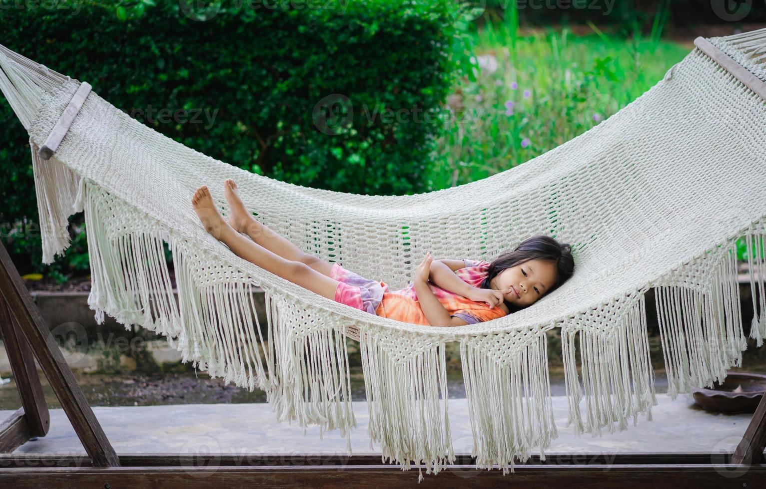 niña asiática en vestido tendido en la cuna foto