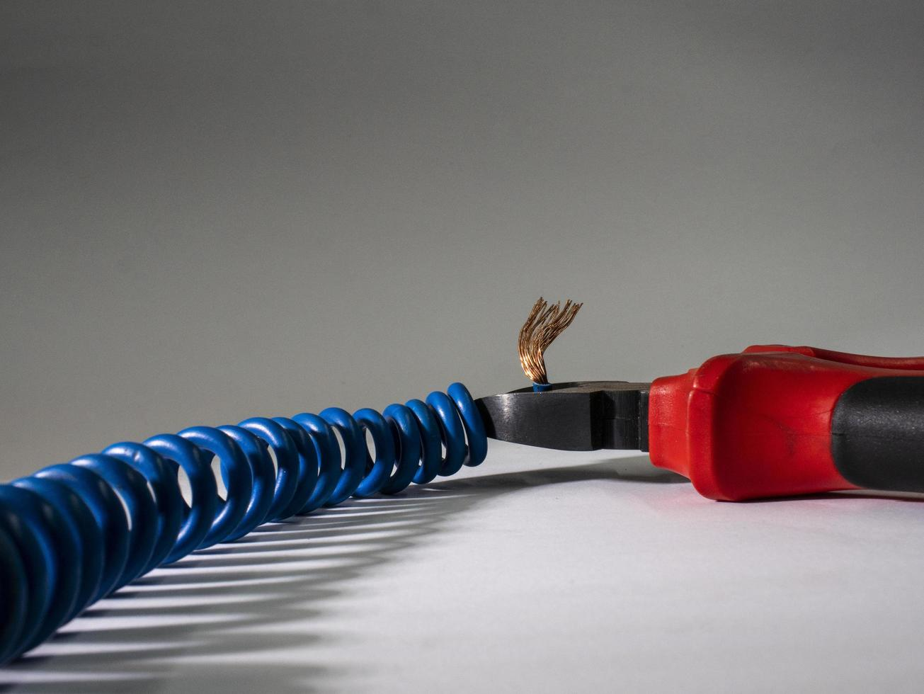 Close up of red pliers and blue twisted wire on white background.Pliers cutting cable photo