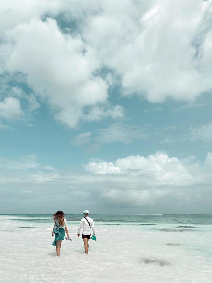 Back view of happy young couple walking on a deserted tropical beach with bright clear blue sky photo