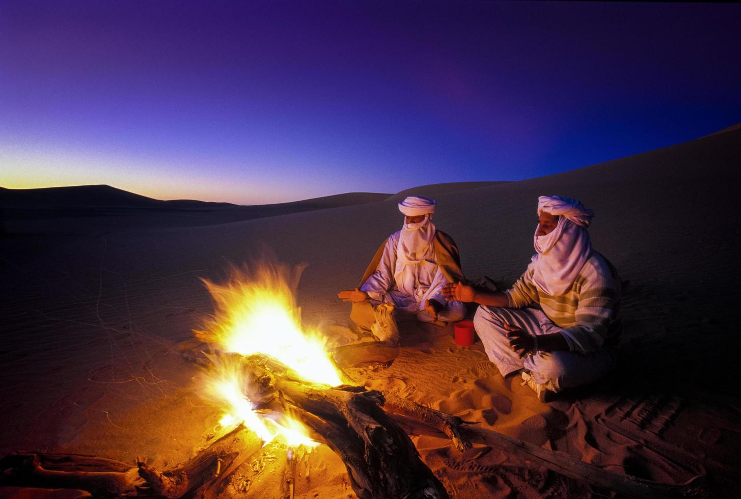 Tikobaouine Algeria 2010- Unknown people in front of the fire at sunset in the Tassili n'Ajjer desert photo