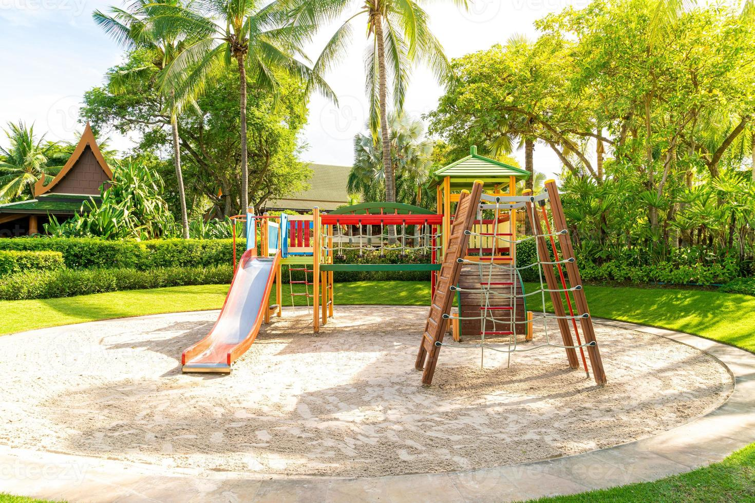 A children's playground, a slider located on the sand photo