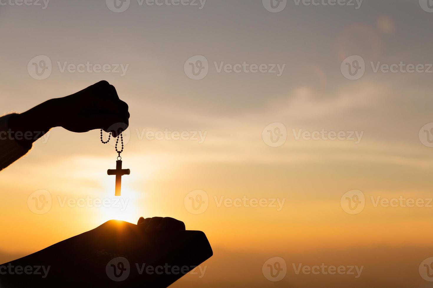 Silhouette of young woman hands holding holy Bible and lift of christian cross with light sunset background. photo