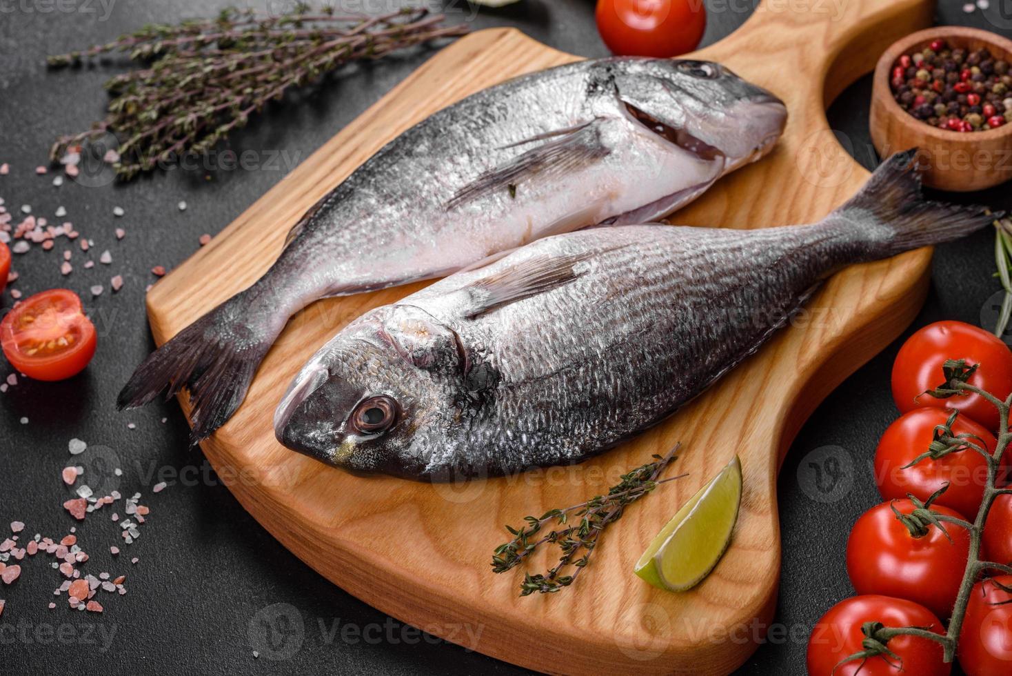 Pescado dorado crudo con especias para cocinar en la tabla de cortar. dorado de pescado fresco foto
