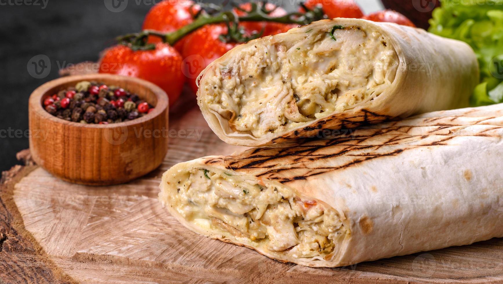 Delicioso shawarma fresco con carne y verduras sobre una mesa de hormigón oscuro foto