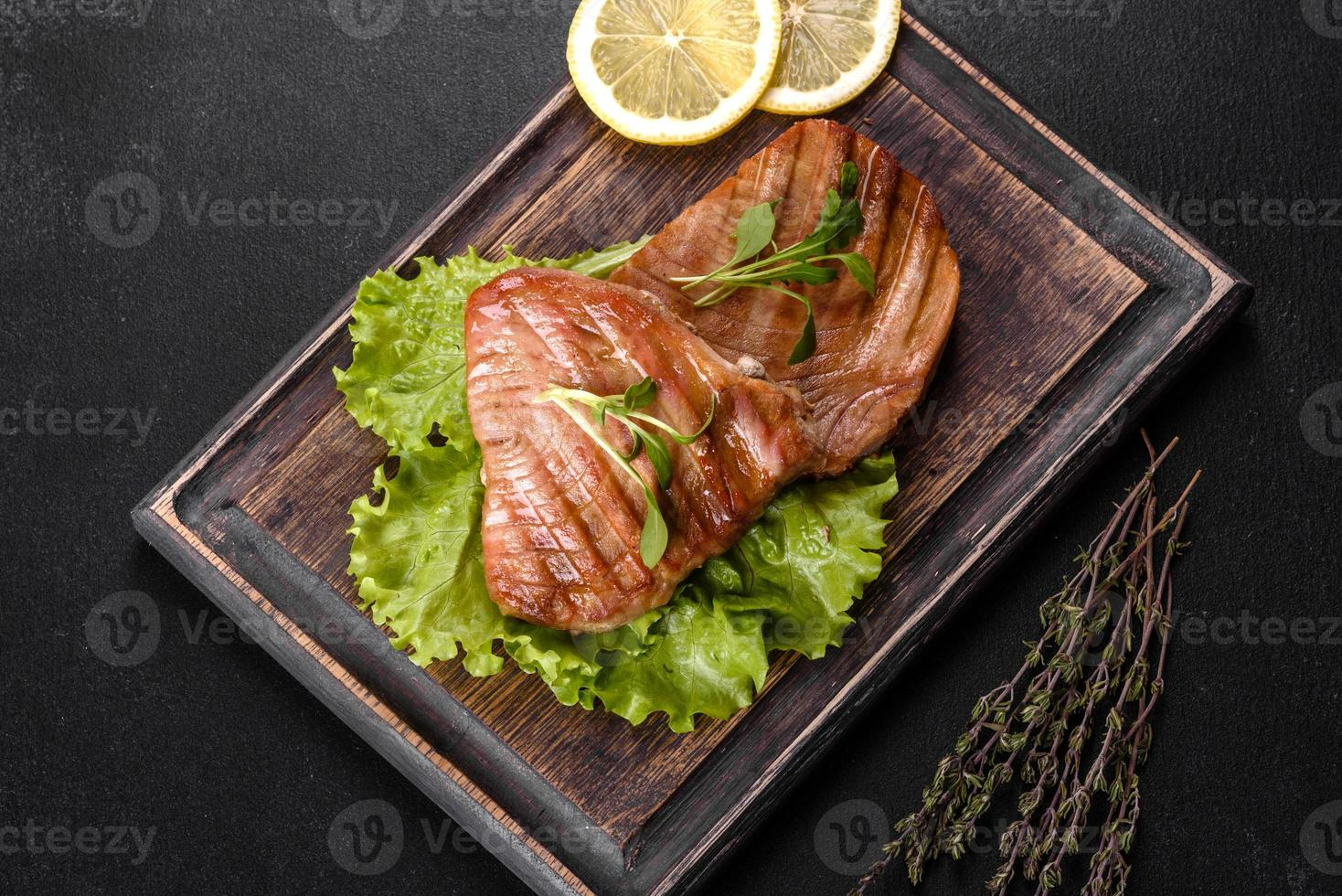 Delicious juicy tuna steak grilled with spices and herbs photo
