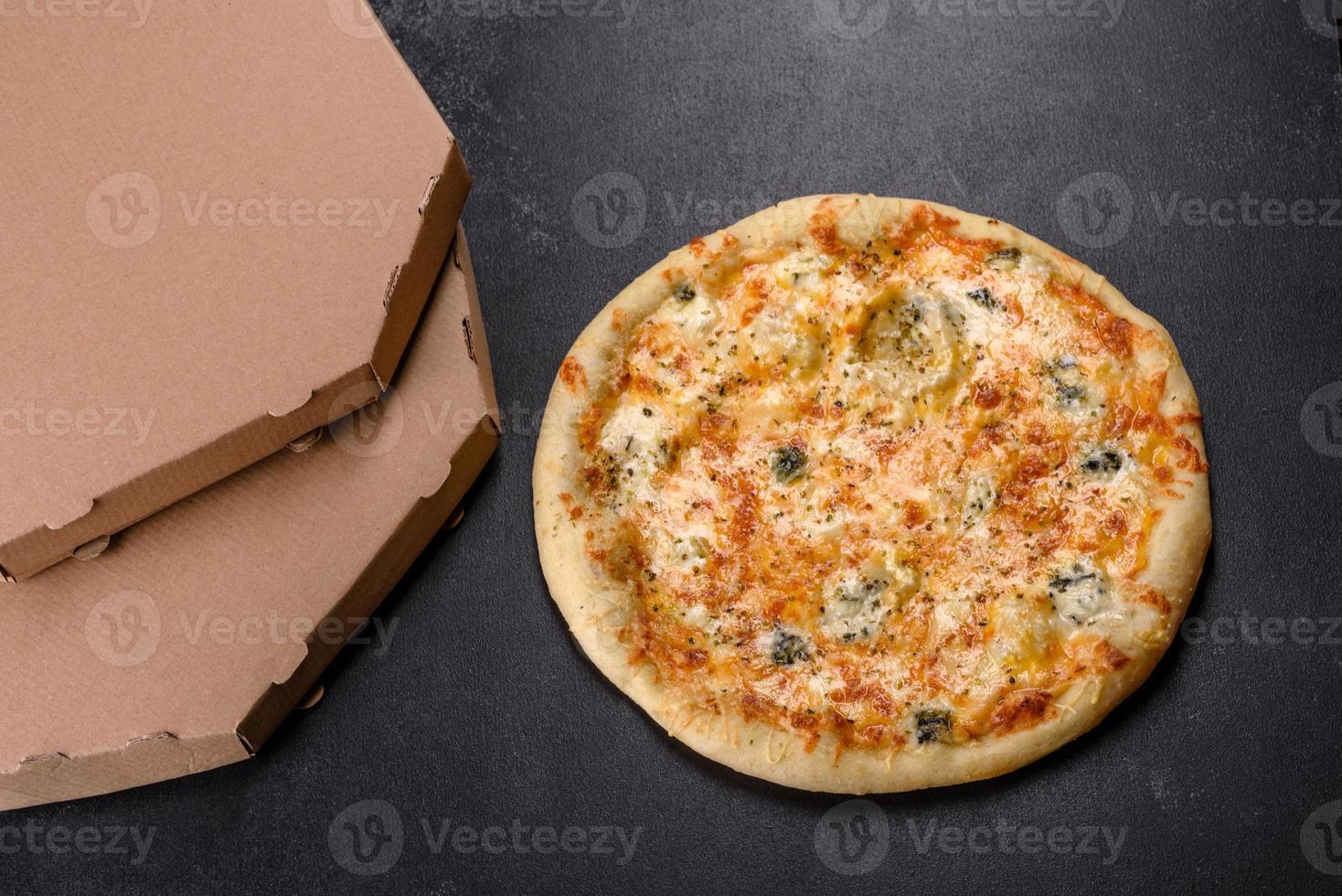 Sabrosa pizza fresca al horno con tomates, queso y champiñones sobre un fondo de hormigón oscuro foto