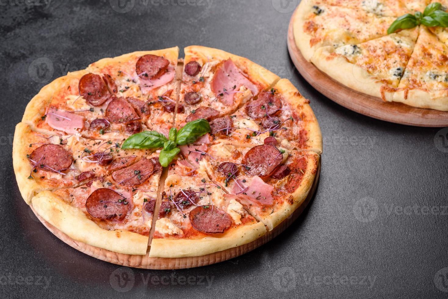 Delicious fresh oven pizza with tomatoes, salami and bacon on a dark concrete background photo