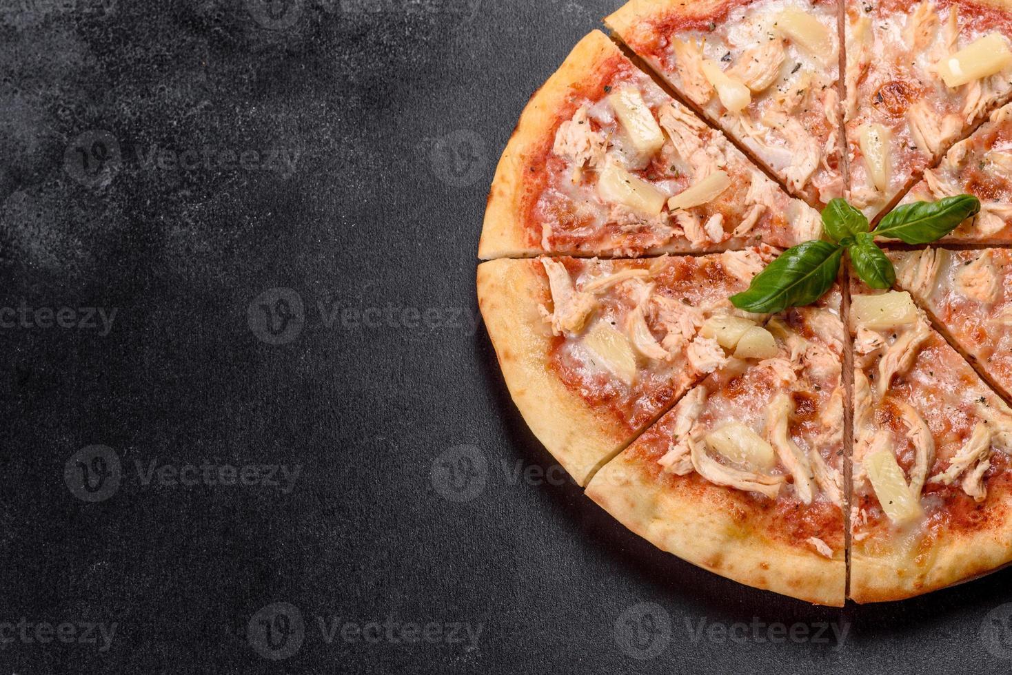 Sabrosa pizza recién horneada con tomate, queso y piña sobre un fondo de hormigón oscuro foto