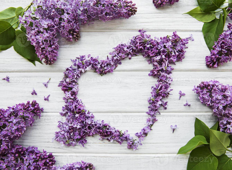 Marco de ramas y flores de color lila en forma de corazón. foto