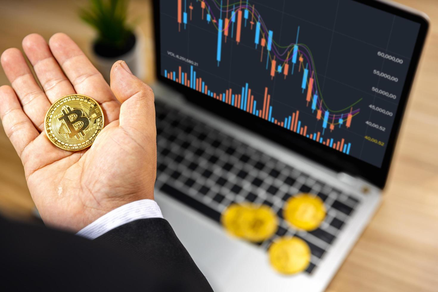 Business bitcoin on hand of investor with graph chart on laptop on wood table, stock market and forex finance concept photo