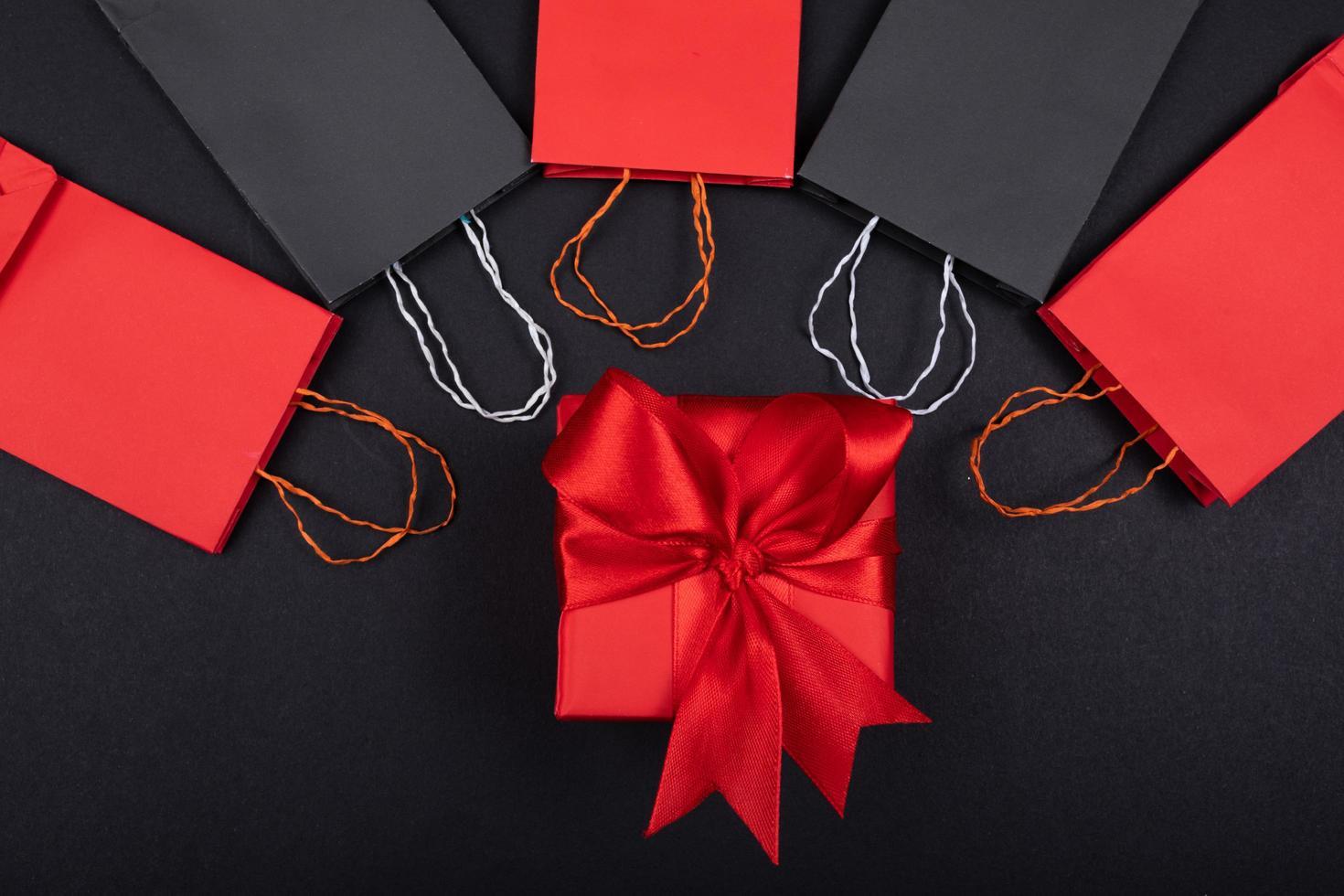 Bolsa de compras colorida en papel de fondo con caja de regalo foto