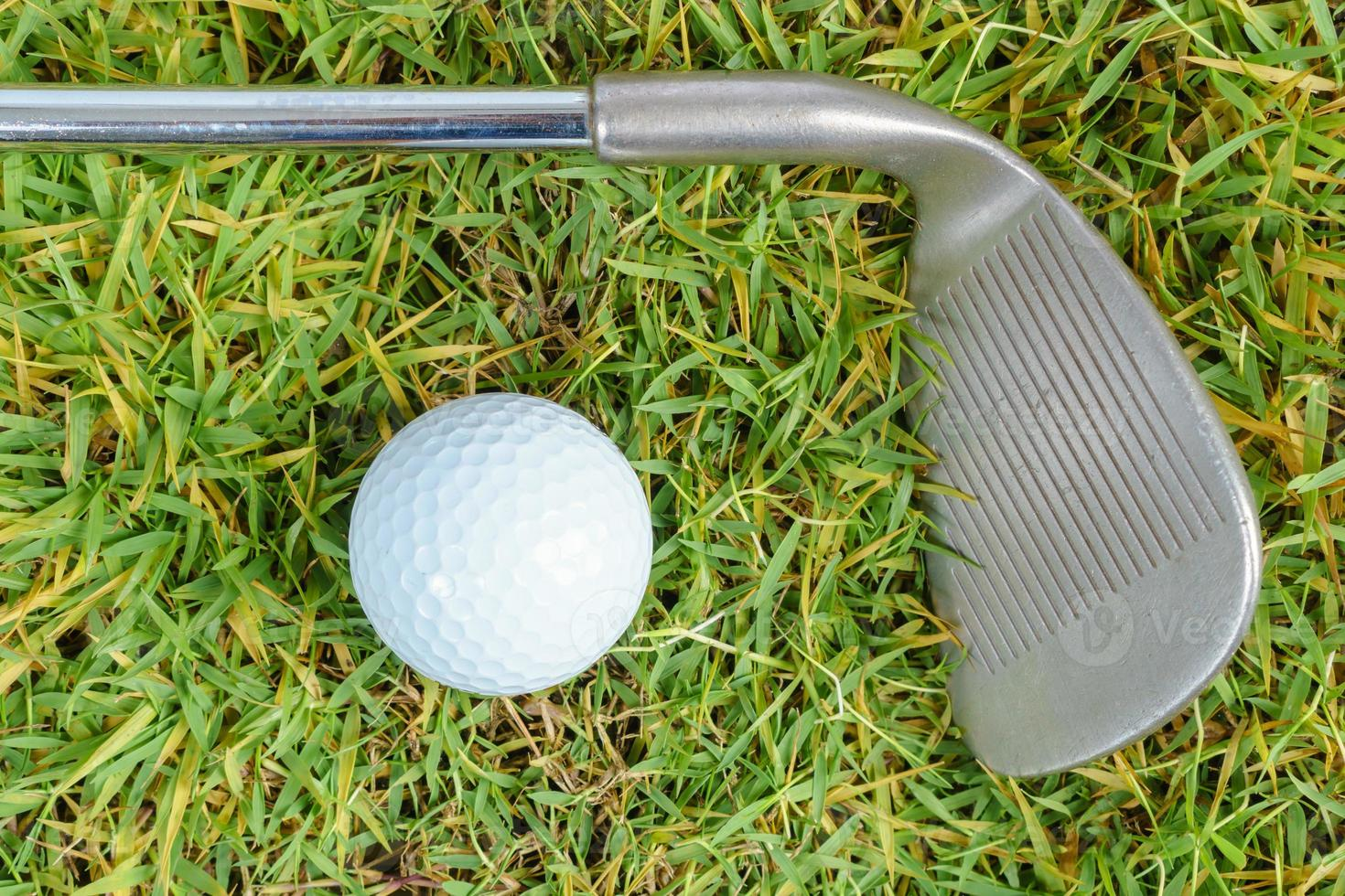 Golf clubs and golf ball on green grass background photo