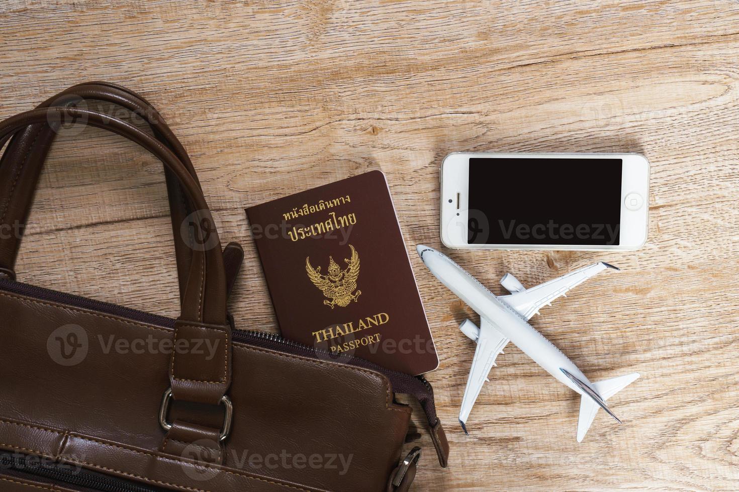 Bolso de cuero y modelo de avión pequeño sobre fondo de tablero de madera foto