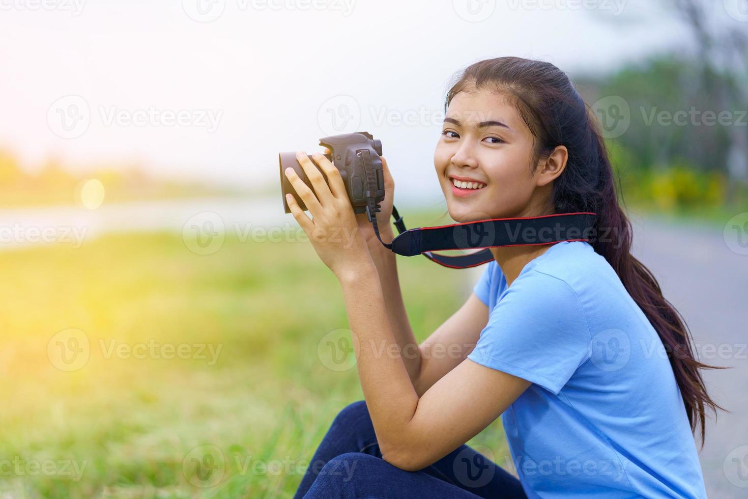 Retrato de una hermosa niña sonriendo con una cámara en las manos foto