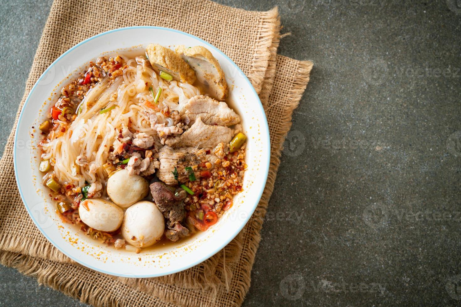 Noodles with pork and meatballs in spicy soup or Tom yum noodles in Asian style photo