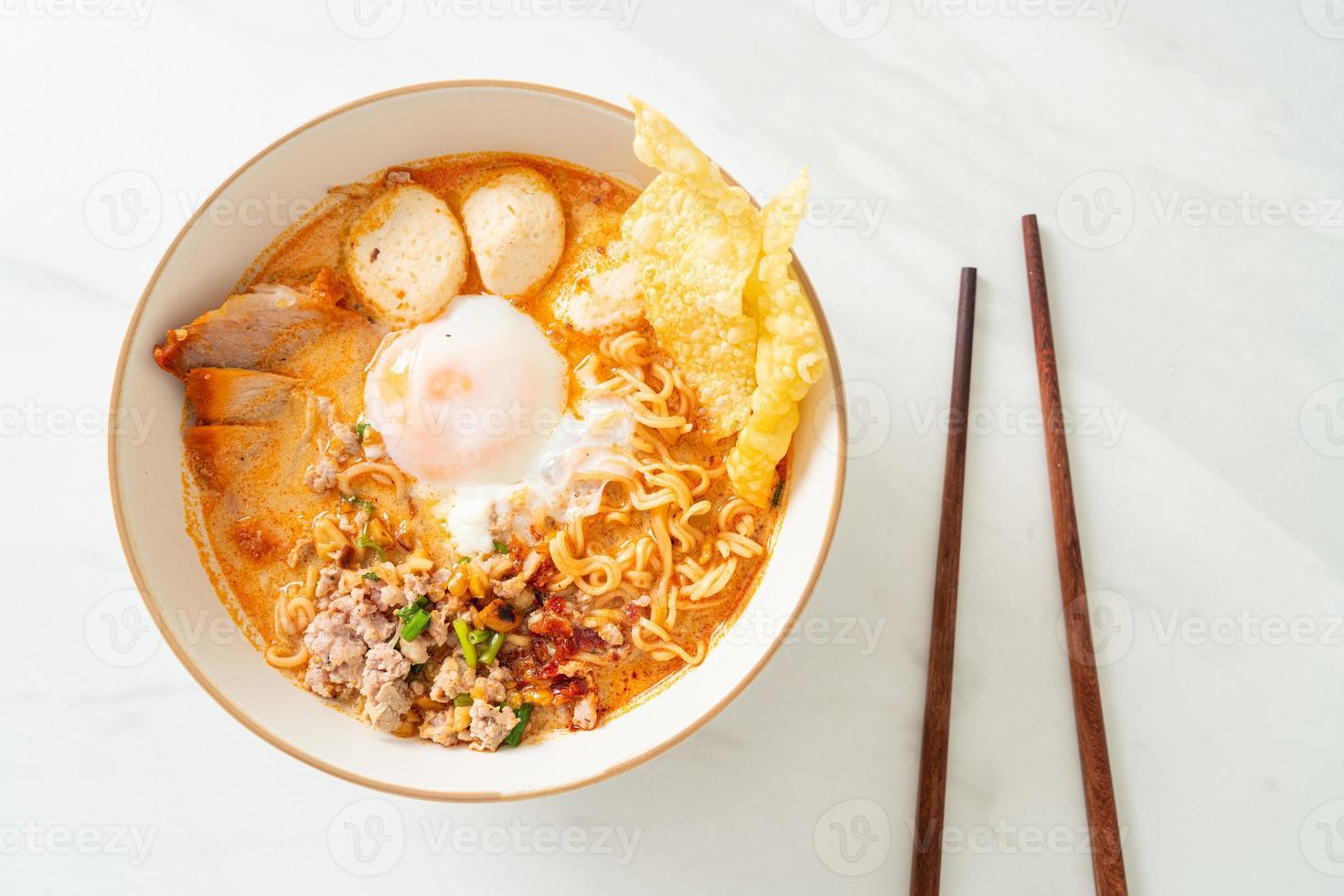 fideos instantáneos con carne de cerdo y albóndigas en sopa picante o fideos tom yum al estilo asiático foto