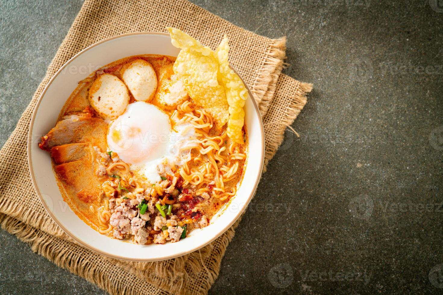 Instant noodles with pork and meatballs in spicy soup or Tom Yum Noodles in Asian style photo