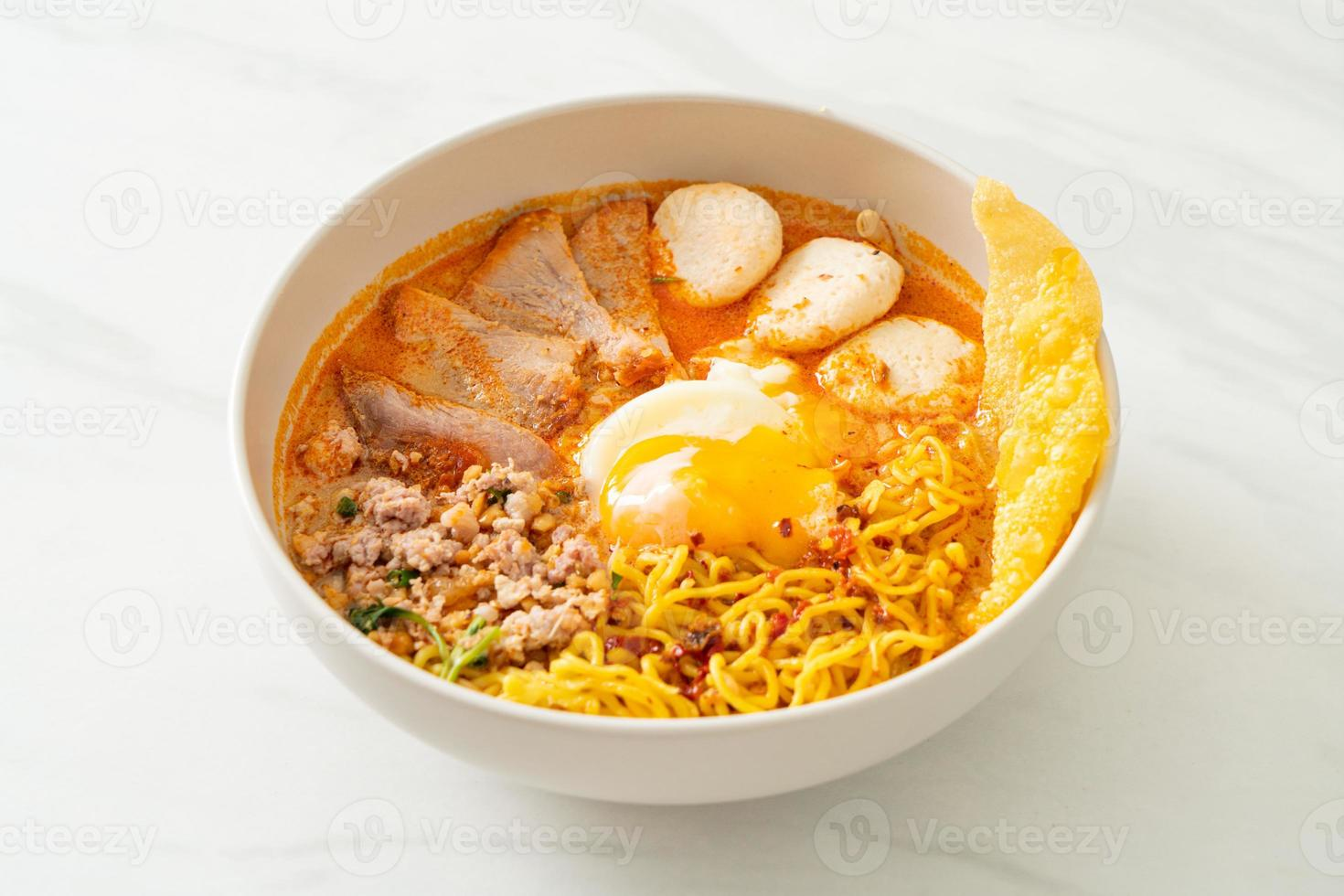 Egg noodles with pork and meatball in spicy soup or Tom Yum Noodles in Asian style photo