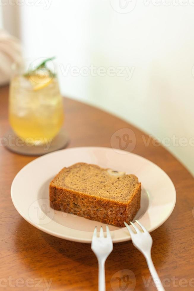 Banana cake on plate in cafe restaurant - soft selective focus point photo