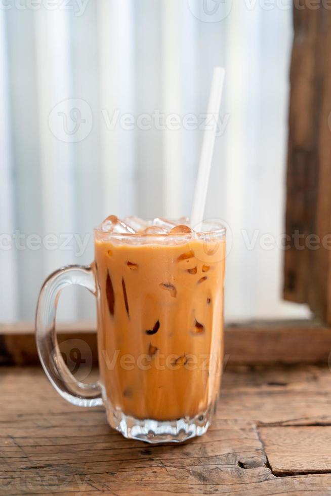 Vaso de té con leche tailandés helado en café restaurante foto