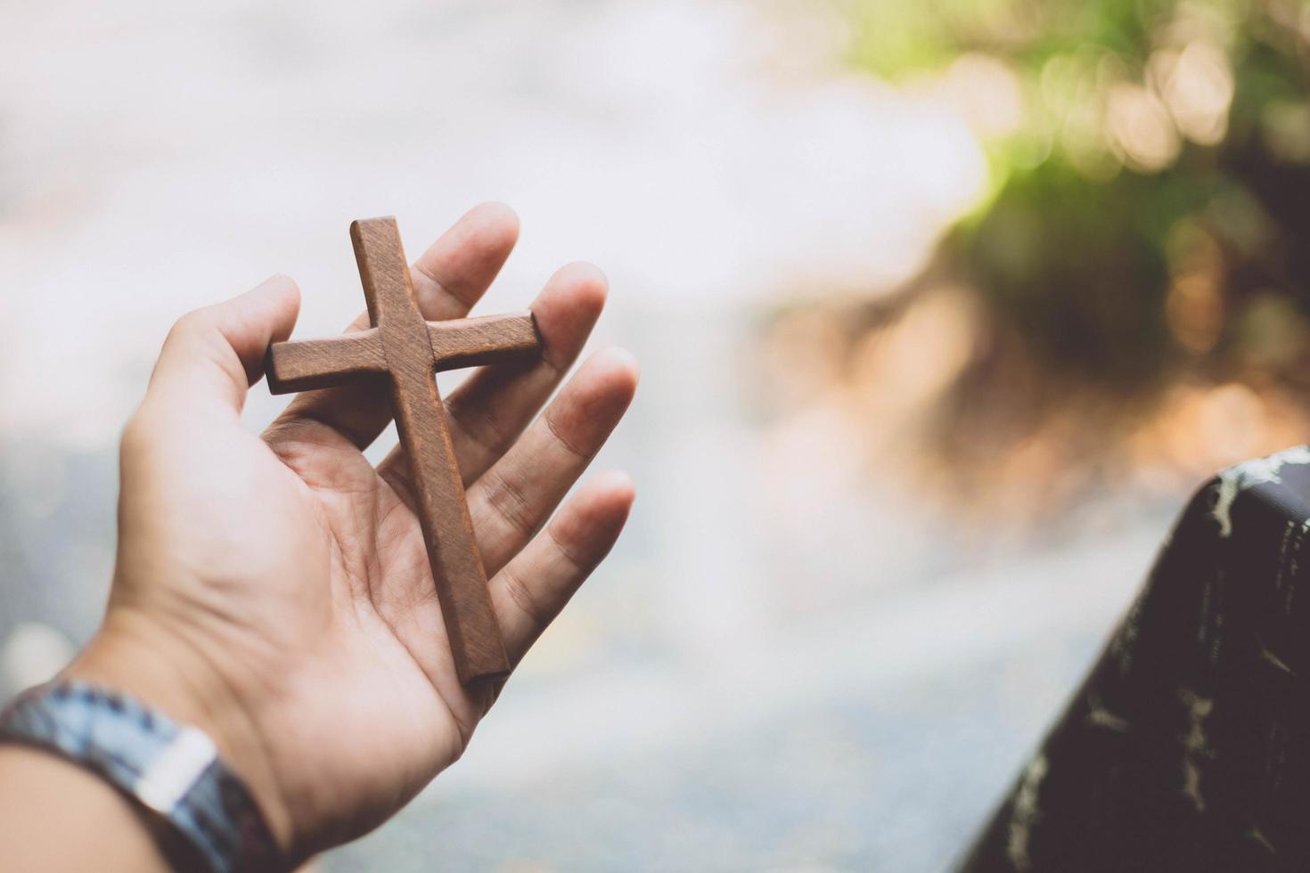 mano que sostiene la cruz de madera con fondo borroso foto