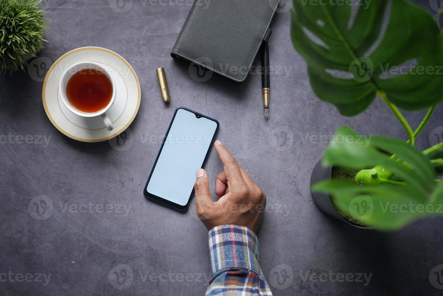 Vista superior de la mano del hombre con teléfono inteligente sobre fondo negro foto