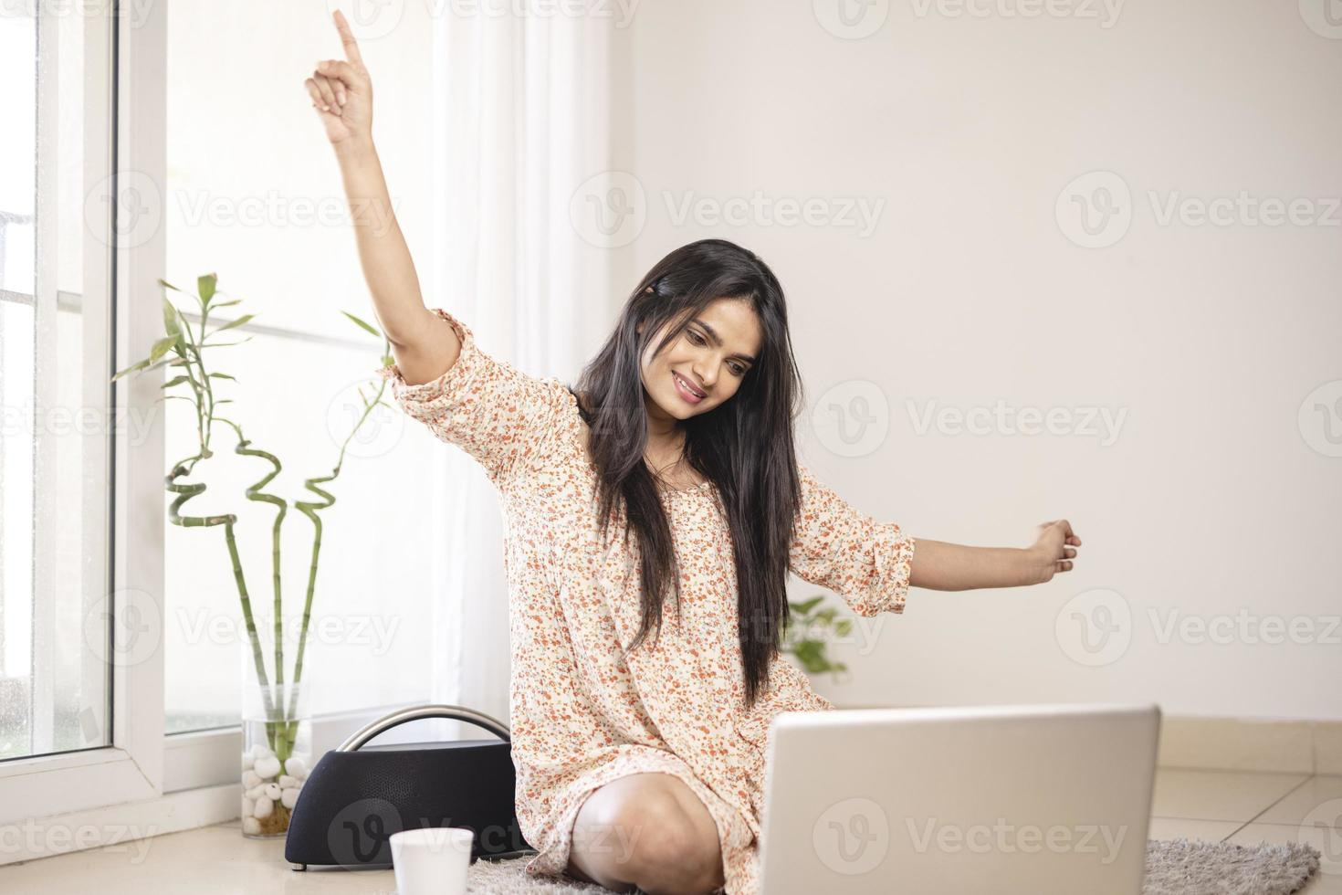 Exited young Indian woman with laptop at home. photo