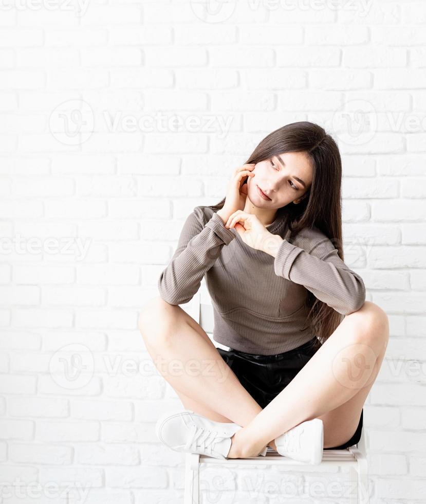 Mujer con cabello largo sentado sobre fondo de pared de ladrillo blanco, pensando foto