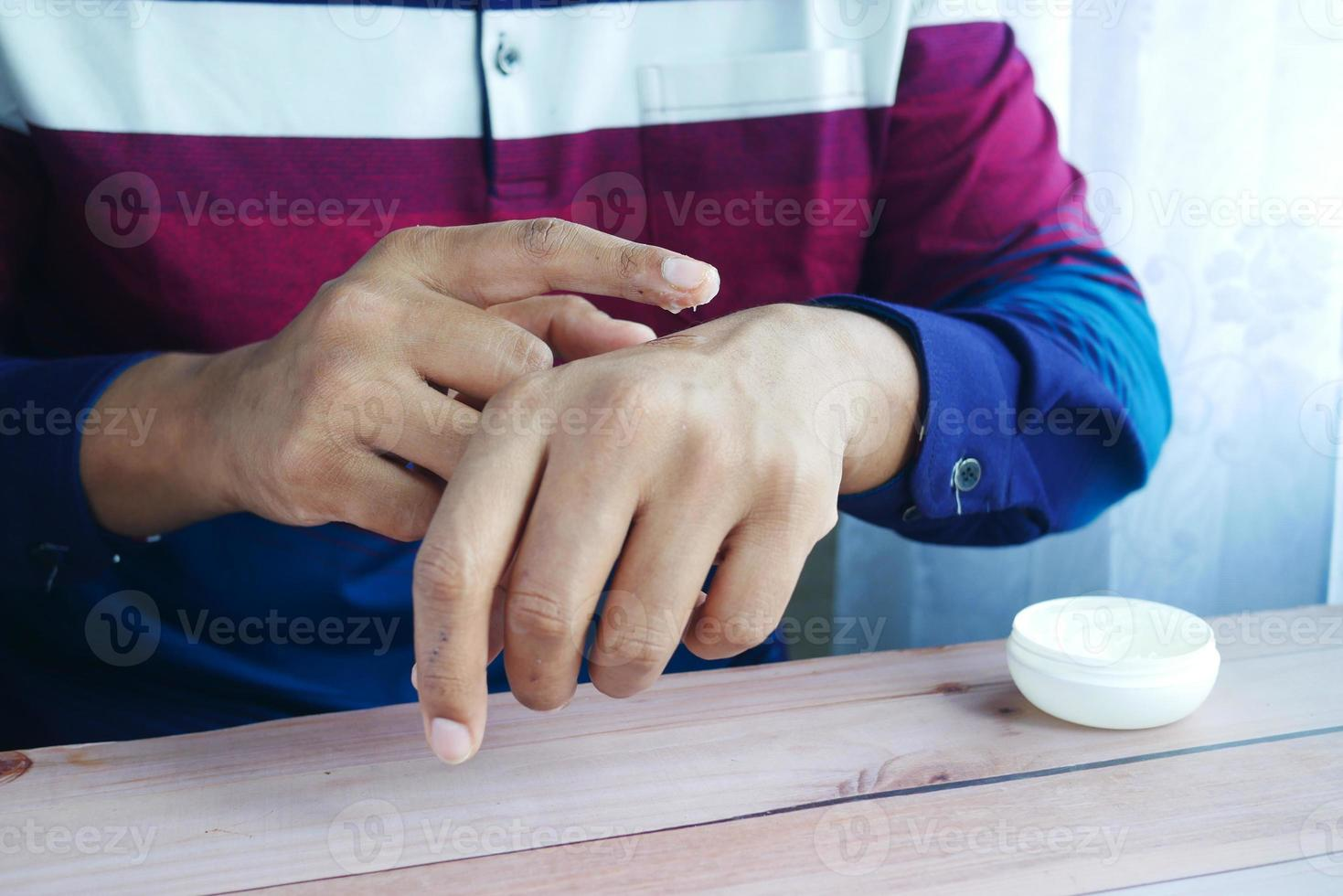 Close up of man hand using petroleum jelly photo