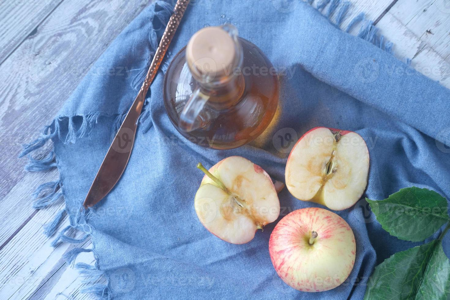 apple vinegar in glass bottle with fresh green apple on table photo