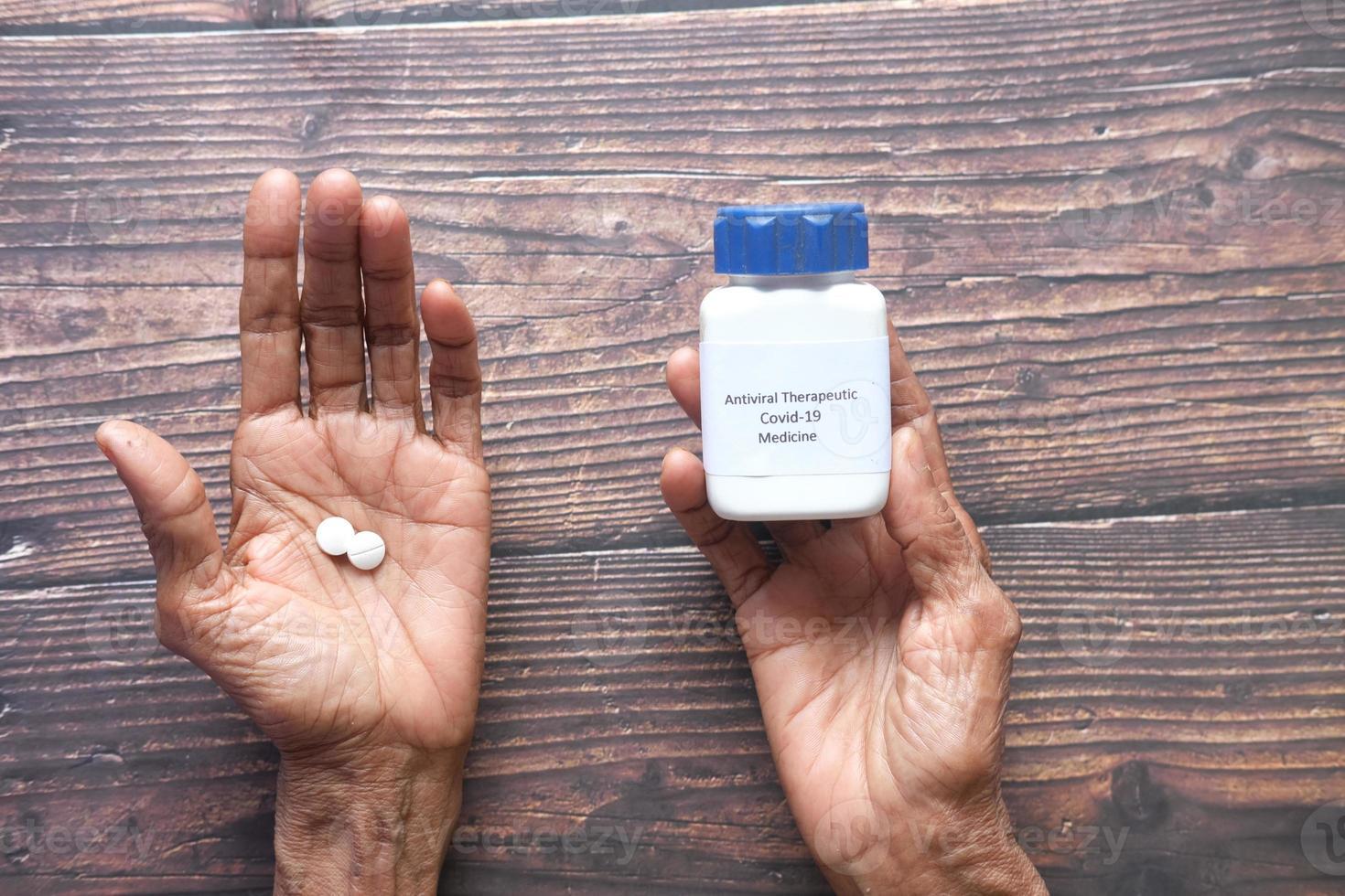 senior women hand hold covid 19 medical medial pills on table photo